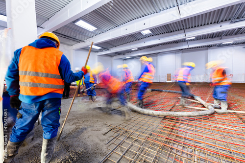 Fotografie, Obraz Workers do concrete screed on floor with heating in a new warehouse building