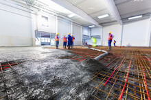 Workers Do Concrete Screed On Floor With Heating In A New Warehouse Building