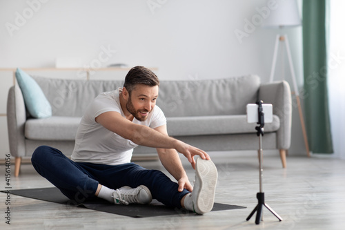 Carta da parati Cheerful sporty man stretching on fitness mat, broadcasting with smartphone