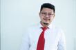 Portrait of a handsome Asian man wearing glasses. Wear a white shirt and red tie.