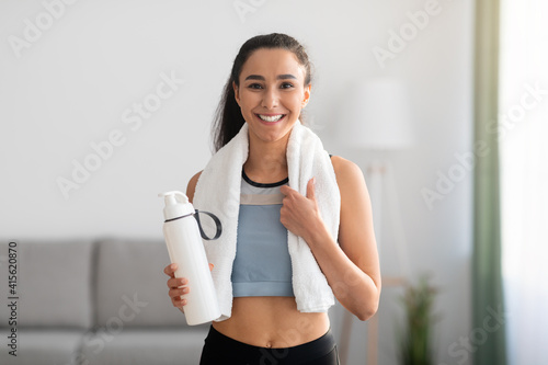 Canvas Print Cheerful brunette woman having break after training at home