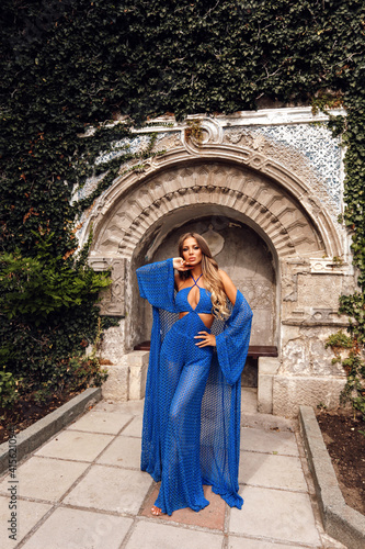Fototapeta beautiful woman with blond hair in elegant clothes posing in antic historical place obraz