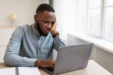 Unhappy Black Businessman Looking At Laptop Sitting At Workplace Indoor