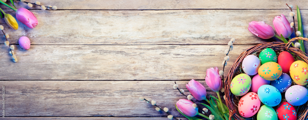 Fototapeta Easter Decoration - Painted Eggs In Basket With Tulips On Natural Wooden Plank
