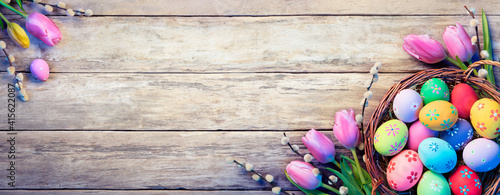 Easter Decoration - Painted Eggs In Basket With Tulips On Natural Wooden Plank