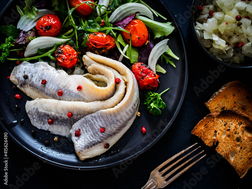 Fototapeta Marinated herrings with roast cherry tomatoes and fresh vegetable leaves on black table  obraz