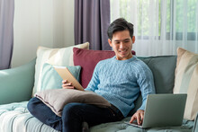 Young Asian Man On A Leisurely Day Sitting Home On Sofa Using Laptop And Tablet On The Couch.