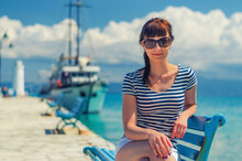 Close-up View Of Young Beautiful Girl With Striped Shirt And Sunglasses Smile And Sit On Bench In Pier, White Ship On Toroneos Gulf Turquoise Water In Halkidiki In Sunny Day, Vacation In Greece