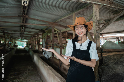 Fotografía cowboy woman posing with both hands offering something while wearing a hat in a