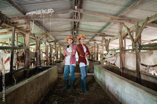Fotografija Two cattle breeders wearing casual clothes and hats stand back to back and pose