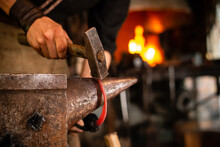 A Blacksmith Forging Horseshoe With Hammer. Blacksmith Forges A Horseshoe In A Forge On An Anvil A Forging Furnace With Fire At The Background.