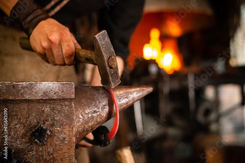 Photographie A blacksmith forging horseshoe with hammer