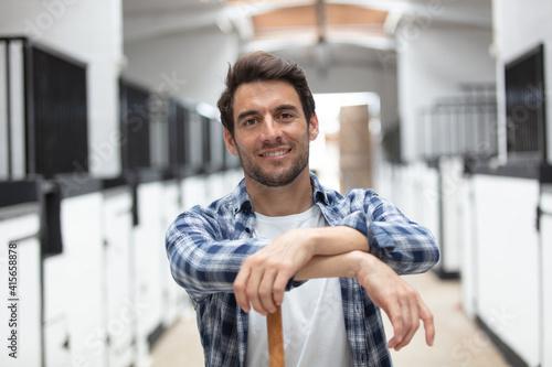 Fotografie, Obraz good looking worker posing in stable