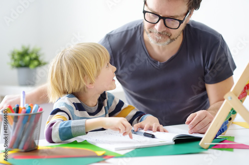 Fototapeta Father helping child do his homework at home. Homeschooling, distance learning, online studying, remote education for kids during quarantine is a problems for parents. Tutor teaching boy with ADHD. obraz