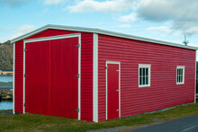 The Exterior Corner View Of A Vintage Red Storage Building. The Old Wooden Structure Has Wood Siding On The Walls, Two Small Windows And A Single Closed Red Wood Door. Green Grass Is On The Ground.