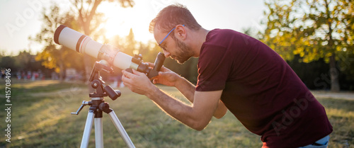 Canvas Print Amateur astronomer looking at the sky with a telescope.