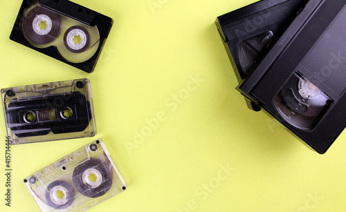 Fotografia, Obraz Three audio tapes and two video tapes on a yellow background