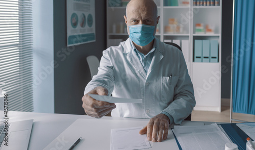 Doctor with surgical mask giving a prescription © stokkete