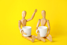 Wooden Mannequins With Cups On Color Background