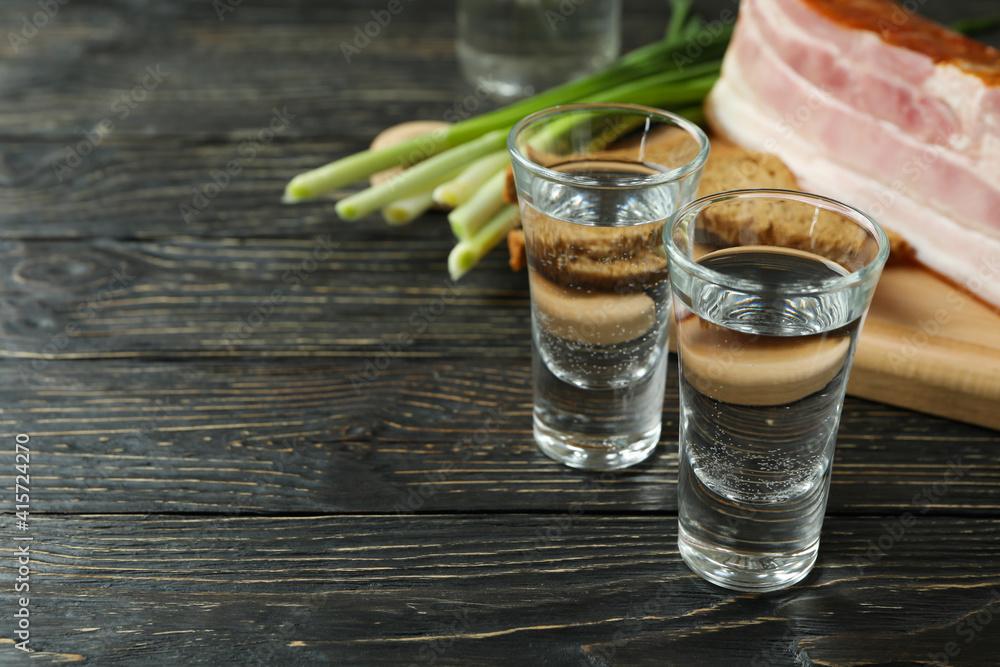 Fototapeta Vodka, onion, bacon and bread on wooden background