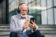 Happy Senior Businessman Is Relaxing After Work In Front Of Company Building. He Is Messaging On Smartphone.