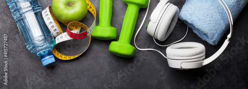 Canvas Fitness concept. Dumbbells, headphones and apple