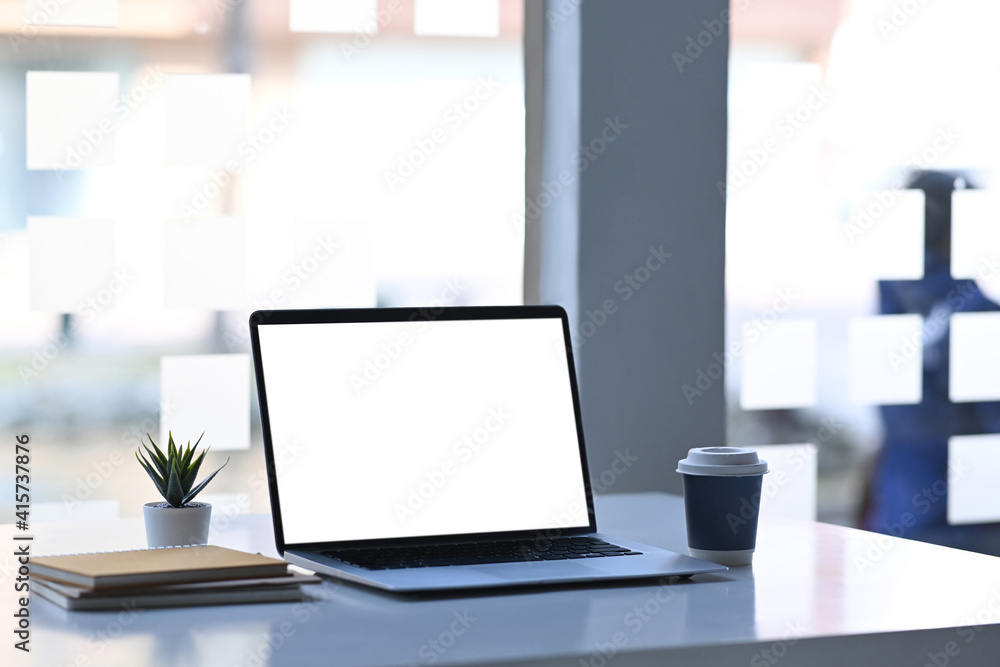 Fototapeta Computer laptop with blank screen , notebook, coffee cup and plant on white table.