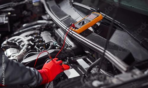 Fotografia Mechanic checking voltage of car battery