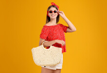 Beautiful Young Woman With Stylish Straw Bag On Yellow Background