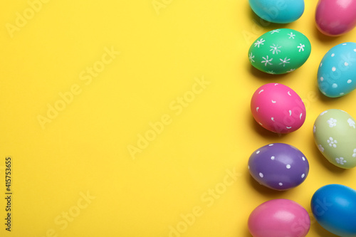 Fototapeta Bright painted eggs on yellow background, flat lay with space for text. Happy Easter obraz