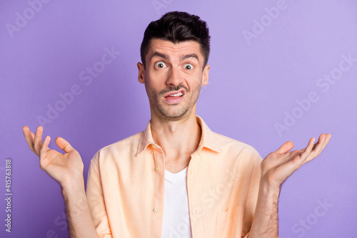 Fototapeta Photo of annoyed mad guy raise palms grimacing staring wear beige shirt isolated violet color background obraz