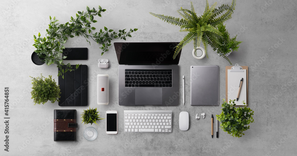 Fototapeta Flat lay top view office desk working space with laptop and office supplies on dark background.