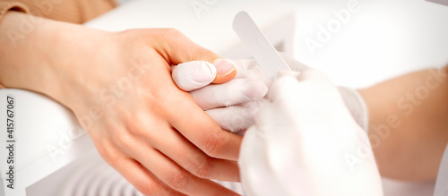 Manicure master wears white gloves with nail file doing manicure on female finge Fototapeta