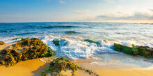 Seascape On A Sunny Morning. Summer Vacation At The Sea. Water Washes Sandy Beach With Rocks. Fluffy Clouds On The Sky