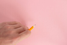 Hand Holds A Pencil On A Colorful Background