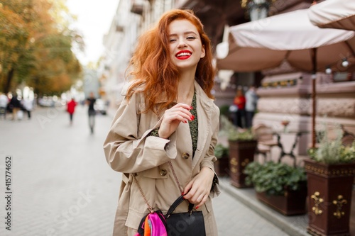 Fototapeta Romantic woman with red hairs and bright make up walking on the street