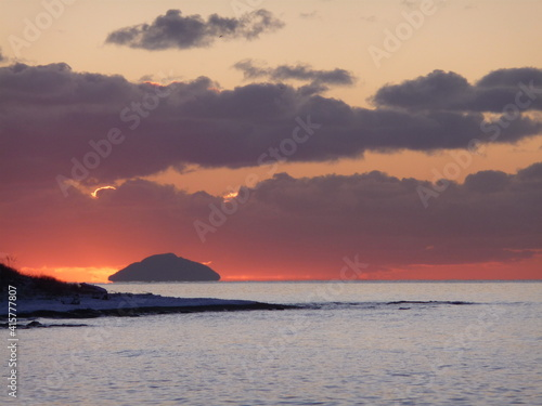 Leinwand Poster Sun setting behind Ailsa Craig, as seen from Prestwick beach, Ayrshire on a cold