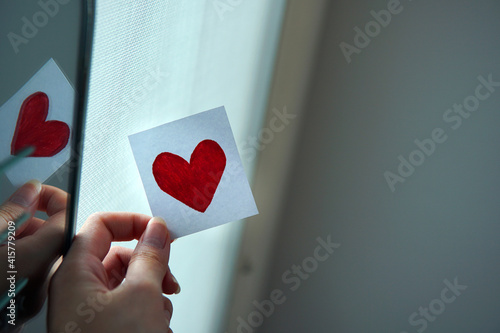 Canvas Print Woman's Hand holding hand draw red heart on sliced piece of white paper near window and natural light with reflection from hanging mirror at home