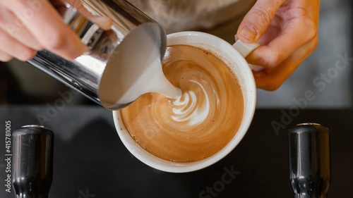 Top view of male barista pouring milk in coffee cups, hand holding a cup of coff Fotobehang