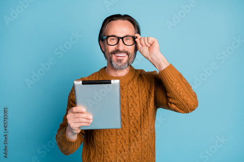 Photo portrait of happy smiling businessman browsing internet tablet wearing glasses isolated on vivid blue color background © deagreez