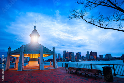 Fotografia East Boston Piers Park Gazebo with lighthouse light in the evening over downtown