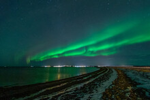 Green Northern Lights On Night Sky With Start Over Winter Landscape. Aurora Borealis Photo Taken In Iceland.