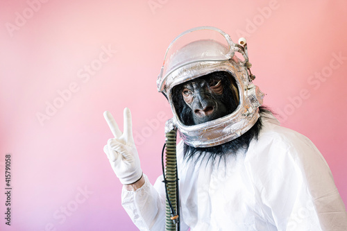 Man with gorilla mask and astronaut helmet showing V-shaped fingers
