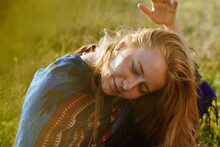 On A Meadow There Sits A Girl In An Ethno Cape Tilting Her Head And Throwing Her Hair Down And Taking Them Over With Her Hand. High Quality Photo