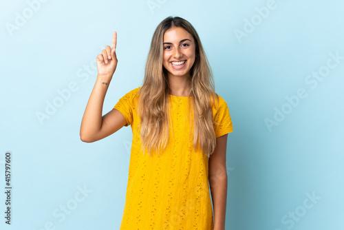 Slika na platnu Young hispanic woman over isolated blue background pointing up a great idea