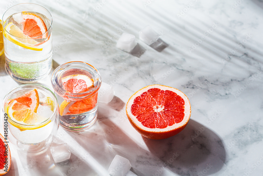Fototapeta Sassy water with grapefruit and lemon, white marble background with dark shadows, copy space.