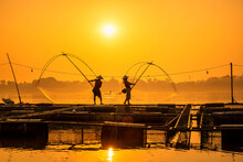 Asian Men And Woman Are Using Nets To Fish In The Mekong River. Fishermen Raising Nile Tilapia, Floating Cages On The Mekong River. Nongkhai, Thailand.