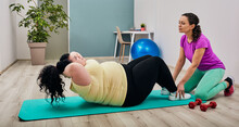 Plus-size Woman Wearing Sportswear Doing Abs Workout On A Mat, Instructor Assisted