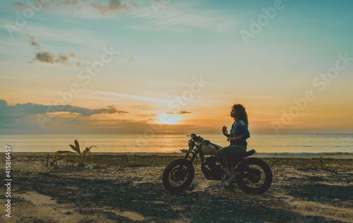 Obraz na plátne Beautiful girl having fun driving her custom cafe racer motorcycle, enjoying the