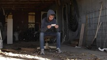 A Teenage Boy Sits In A Dirty Garage Looking At A Picture. The Young Teen Man Looks Sad And Depressed And Is Wearing A Hoodie.